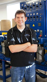 Tony Kulesa. Smiling an wearing bluejeans and black shirt with arms crossed